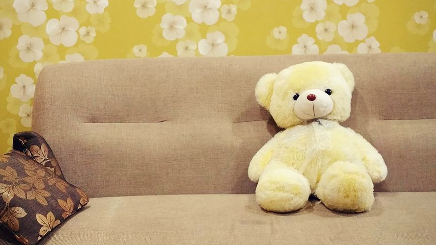 a teddy bear sitting in a sofa