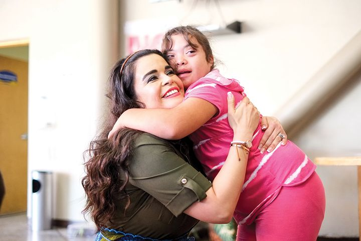 child with down syndrome hugging her teacher
