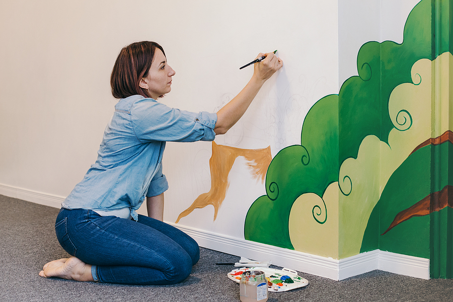 Female mural painter outlining in a wall