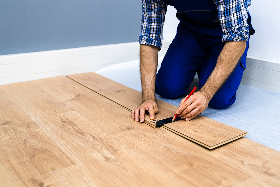 Timber floor installation Melbourne professional doing measurements and adjustments