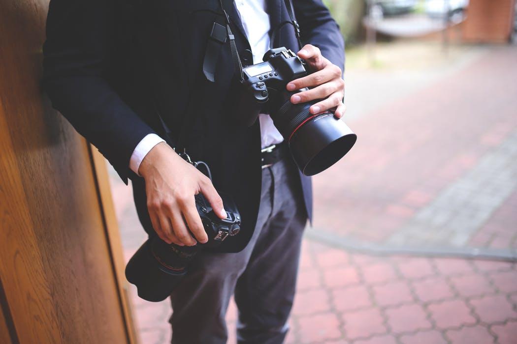 Wedding photographer in Sydney holding a camera